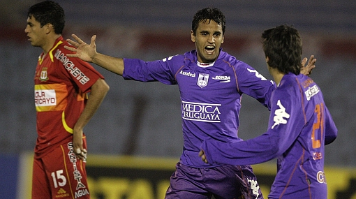 Amado of Defensor Sporting celebrates with teammate Texeira after scoring his team's third goal during their Copa Sudamericana match in Montevideo